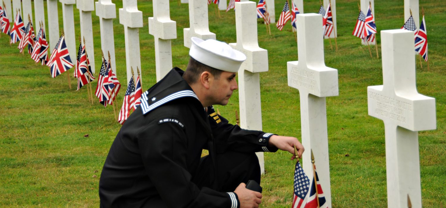Petty Officer 1st Class Samuel Hernandez-Moreno, ship's serviceman, assigned to the aircraft carrier USS George H.W. Bush, pays his respects to a fallen service member buried at the Brookwood American Cemetery and Memorial on Memorial Day. George H.W. Bush is anchored off the coast of Portsmouth, England, for the ship's first overseas port visit of its first combat deployment.
